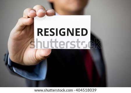 Businessman presenting 'RESIGNED' word on white card - stock photo