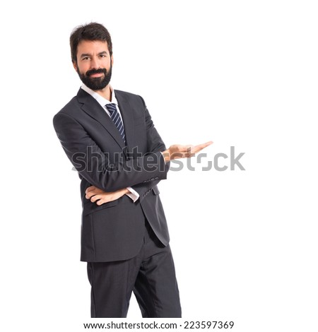 Businessman presenting something over isolated white background - stock photo