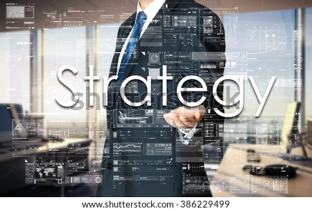 Businessman presenting text Strategy on virtual screen. He is in the office - stock photo