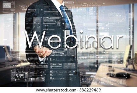Businessman presenting text Webinar on virtual screen. He is in the office - stock photo
