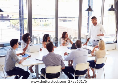 Businessman presenting to colleagues at a meeting - stock photo
