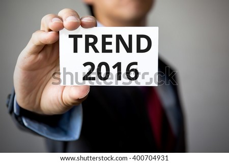 Businessman presenting 'Trend 2016' word on white card - stock photo