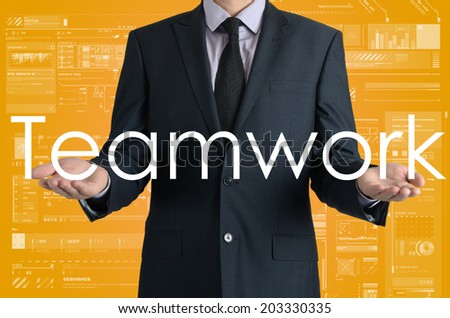 businessman presents a word Teamwork with his own hands - stock photo
