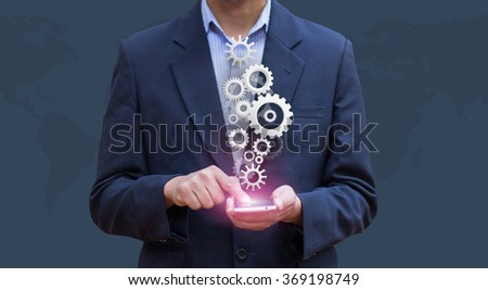 Businessman press smartphone computer show gear. Business Tools and Success as concept. - stock photo
