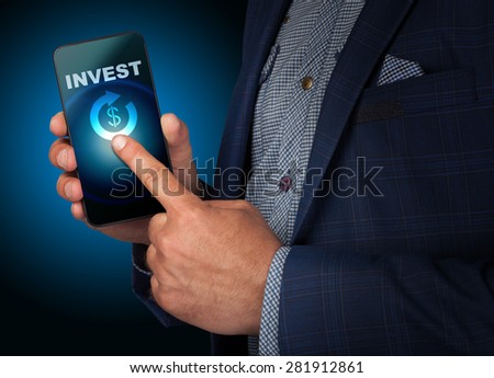 Businessman presses a button touch screen smatrfona invest. Business, technology, internet and networking concept - stock photo