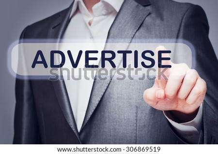 Businessman presses Advertise button on virtual screen. Online marketing concept - stock photo