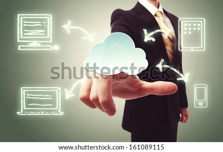 Businessman pressing a cloud icon with devices over vintage green background - stock photo