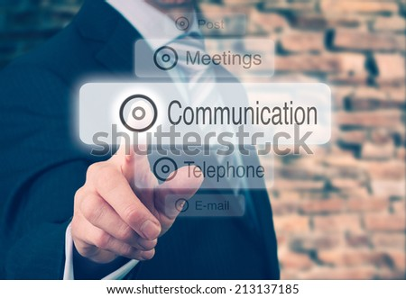 Businessman pressing a Communication concept button. Instagram Styling Applied. - stock photo