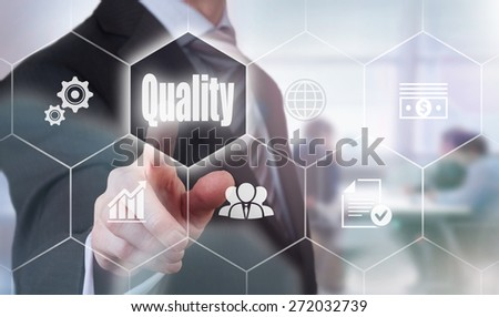Businessman pressing a Quality concept button. - stock photo