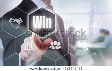 Businessman pressing a Win concept button. - stock photo