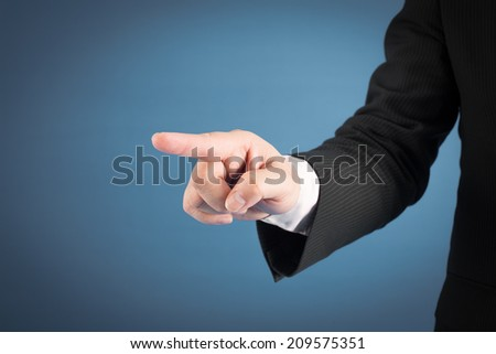 Businessman pressing an imaginary button on bokeh over dark background - stock photo