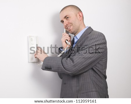 Businessman pressing an intercom with a smile and positive attitude on white background. - stock photo