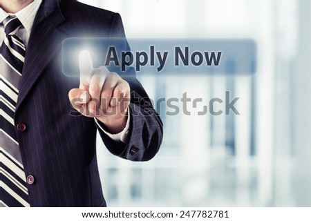 Businessman pressing Apply Now button at his office. Toned photo. - stock photo