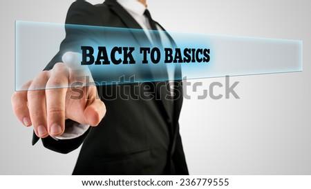Businessman Pressing Back to Basics Text on Transparent Glass. - stock photo