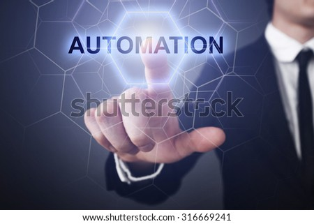 "Businessman pressing button on touch screen interface and select ""auomation""."
