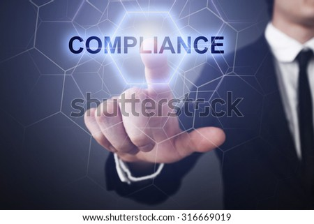 "Businessman pressing button on touch screen interface and select ""compliance""."