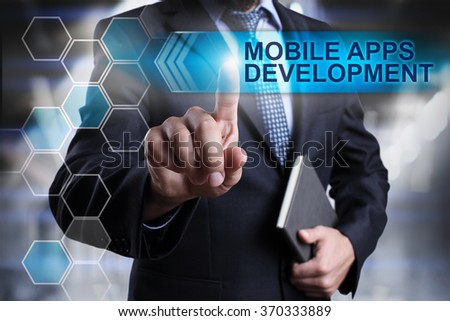 """Businessman pressing button on touch screen interface and select """"Mobile apps development"""". Business concept. Internet concept. - stock photo"""