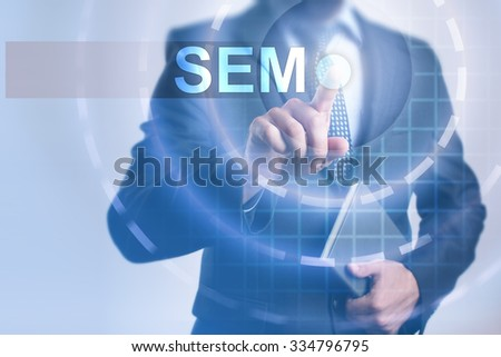 Businessman pressing button on touch screen interface and select SEM. Business, internet, technology concept.