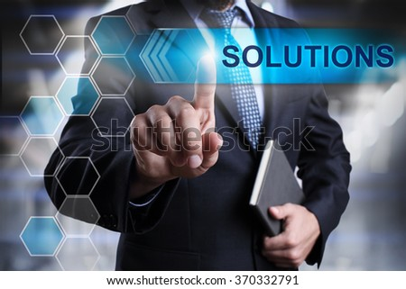 """Businessman pressing button on touch screen interface and select """"Solutions"""". Business concept. Internet concept. - stock photo"""