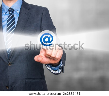 Businessman pressing mail button on visual screen. Customer support concept. Isolated on grey background. - stock photo