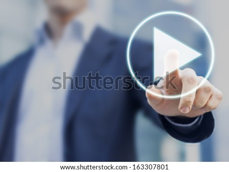 Businessman pressing play button to start or initiate projects - stock photo