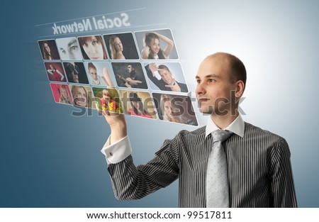 Businessman pressing social buttons on a virtual background - stock photo