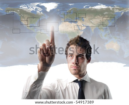 Businessman pressing the cell of a digital graphic with world map on the background - stock photo