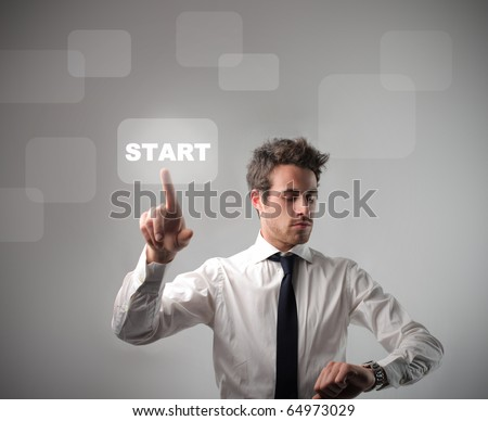 Businessman pressing the start button on a touchscreen