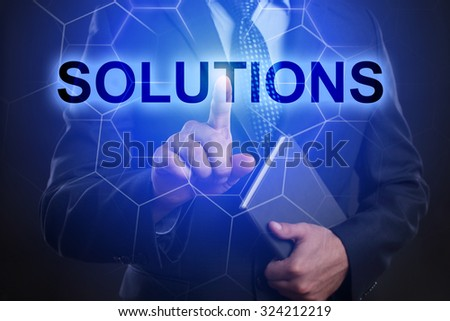 "Businessman pressing touch screen interface and select ""Solutions""."