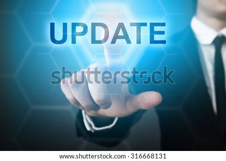 "Businessman pressing touch screen interface and select ""Update""."