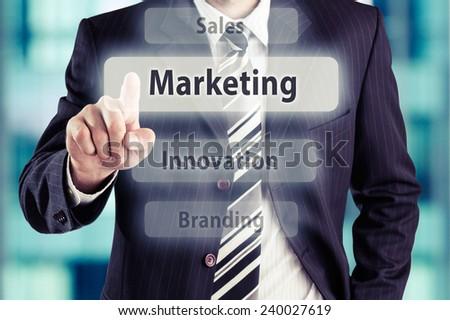 Businessman pressing virtual marketing  button. Marketing concept, toned photo. - stock photo