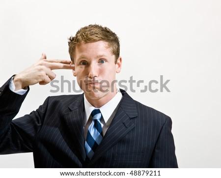Businessman pretending to shoot self in head - stock photo