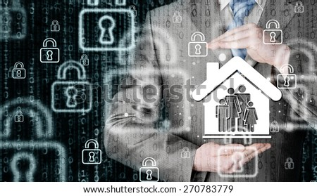 businessman protecting family in home with hands - stock photo