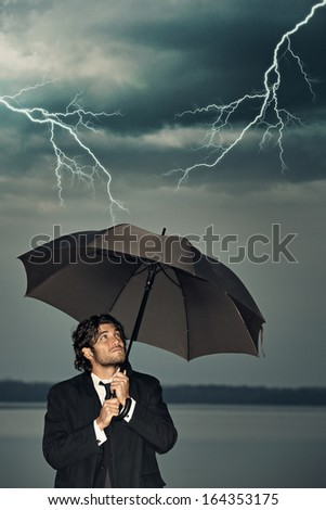 Businessman protecting himself from the storm coming with an umbrella. Dark sky with thunders
