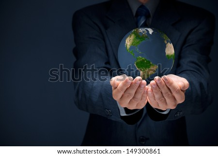 Businessman protecting the Earth: sustainable responsible (eco-friendly) business and global business concepts. Move heaven and earth idiom. Source map by NASA.