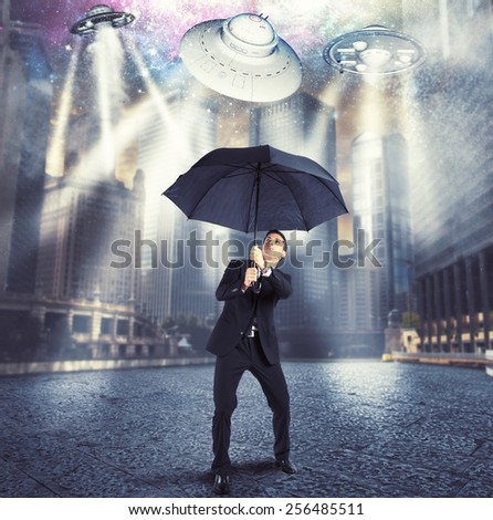 Businessman protects himself from an alien attack - stock photo