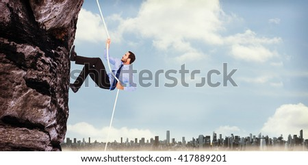 Businessman pulling a rope with effort against large city on the horizon - stock photo