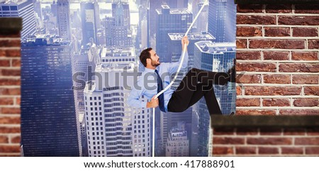 Businessman pulling a rope with effort against red brick wall - stock photo