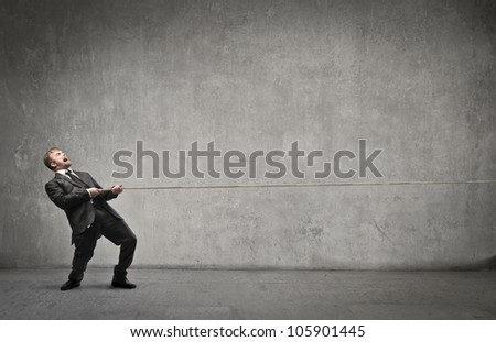 Businessman pulling a rope with evident effort - stock photo