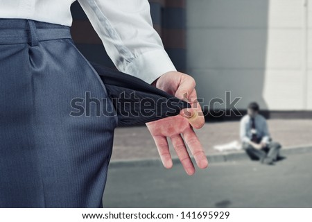 Businessman pulling empty pocket out of pants - stock photo
