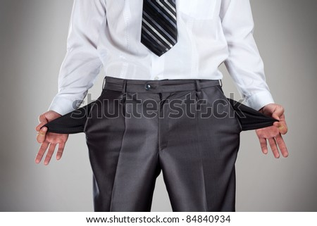 Businessman pulling empty pockets out of pants - stock photo