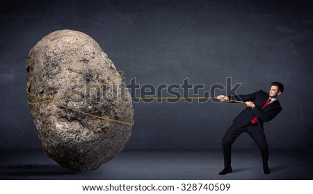 Businessman pulling huge rock with a rope concept on background - stock photo
