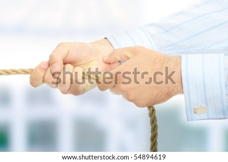 Businessman pulling on a piece of rope. - stock photo