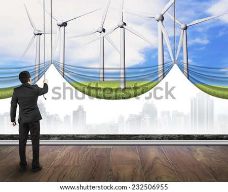 businessman pulling open group of wind turbines curtain covered gray cityscape, environmental protection and alternative energy concept - stock photo