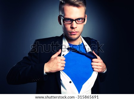 Businessman pulling open his shirt like a superhero - stock photo