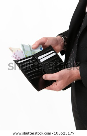 Businessman pulling out a wad of money from his wallet - stock photo