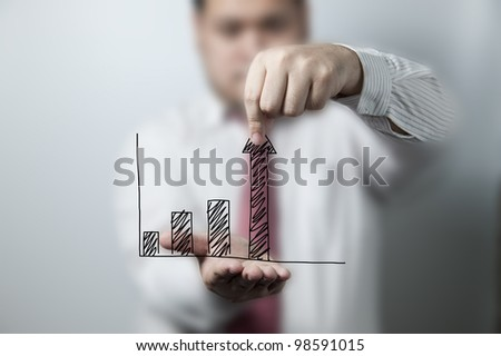 Businessman pulling up a graph - stock photo
