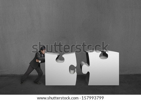 Businessman push two heavy puzzles together in concrete wall background.