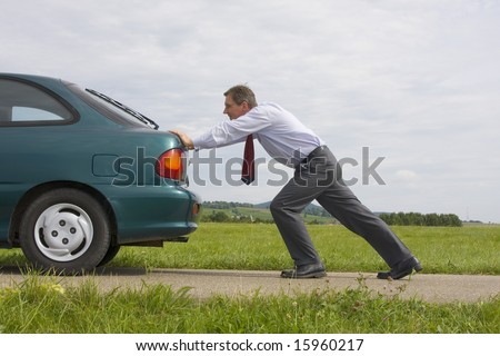 Businessman pushing a car with empty fuel tank - stock photo