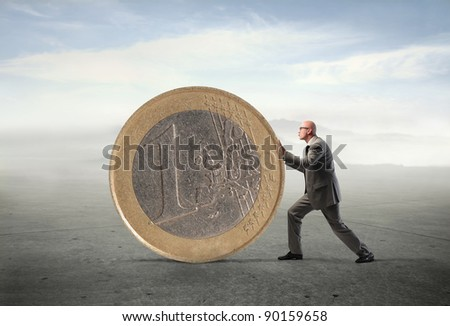 Businessman pushing a giant euro coin - stock photo